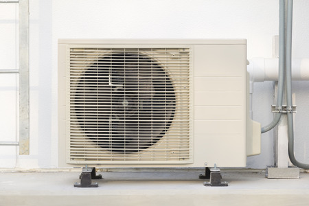 ventilate: Air compressor with white wall background. Stock Photo