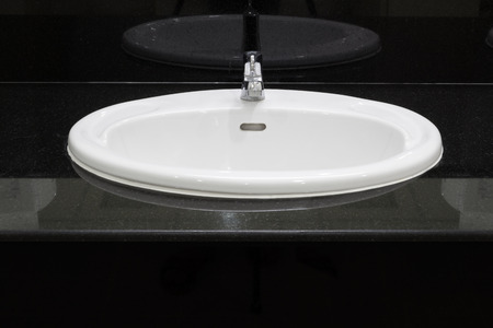 bowl sink: White basin place on granite counter.