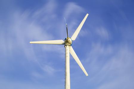 Wind turbine with blue sky background.