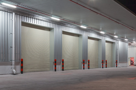 Exterior of factory with shutter door, night time