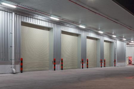 Exterior of factory with shutter door, night time