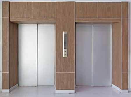 Elevator door with wood wall. photo