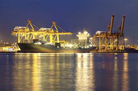 seaports: Cargo ship and crane at port reflect with water, twilight time.