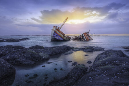 Ancient shipwrecks in the sea with sunset background