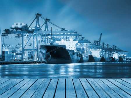 commercial docks: Cargo ship and crane at port reflect with river, twilight time  blue color tone