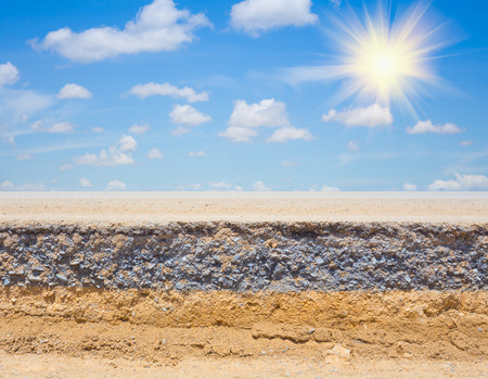 rock bottom: Cross section of asphalt road  (top layer is an asphalt and bottom layer is an crushed rock ) with blue sky background. Stock Photo