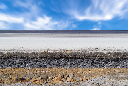 cross cut: Cross section of asphalt road   top layer is an asphalt and bottom layer is an crushed rock   with blue sky background