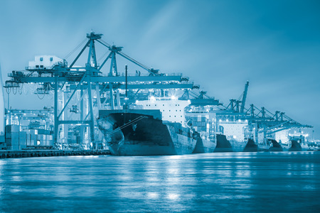 Cargo ship and crane at port reflect with water, twilight time  blue color tone