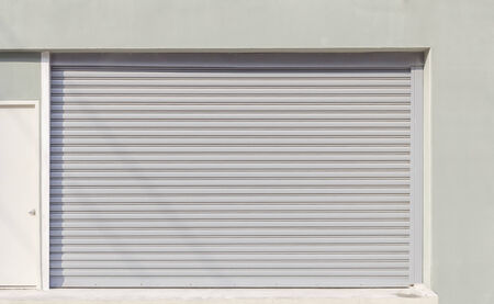 rolling garage door: Shutter door or rolling door (gray color) day scene.  Stock Photo