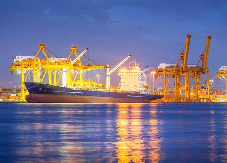 Cargo ship and crane at port reflect with water, twilight time  photo