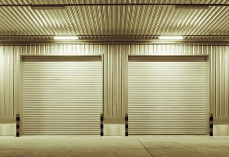 shutter door: Exterior of factory with shutter door, night time.