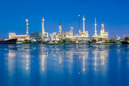 Panorama of oil refinery reflected on river at twilight. photo
