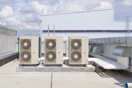 Air compressor op het dak van de fabriek met blauwe hemel achtergrond.