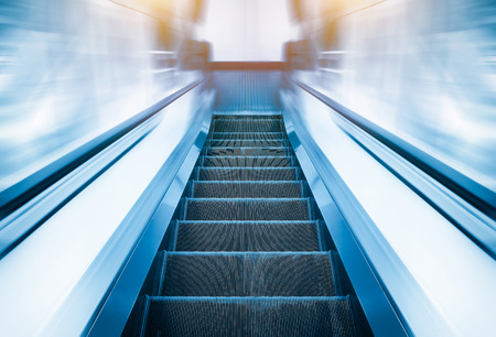 upstairs: Escalator machine, blue color tone. Stock Photo