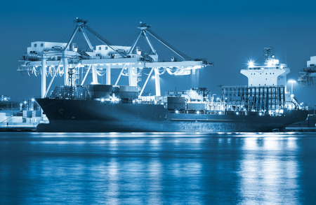 Cargo ship and crane at port reflect with river, twilight time (blue color tone). Stock Photo