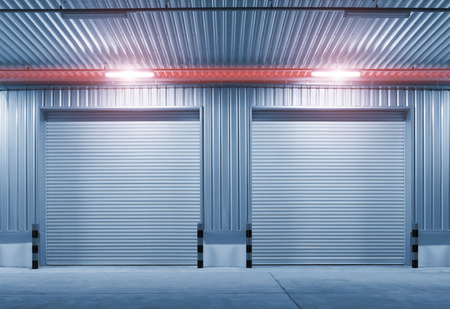 Exterior of factory with shutter door, night time.