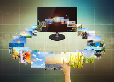advertisment: Hand touch multimedia on screen with modern dark background.