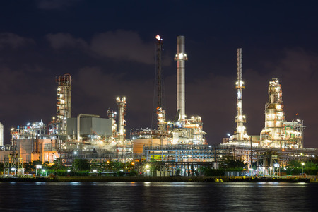 Oil refinery reflected on river at night. photo