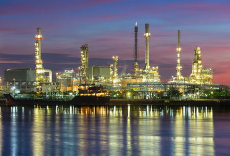 Oil refinery reflected on river at twilight. photo