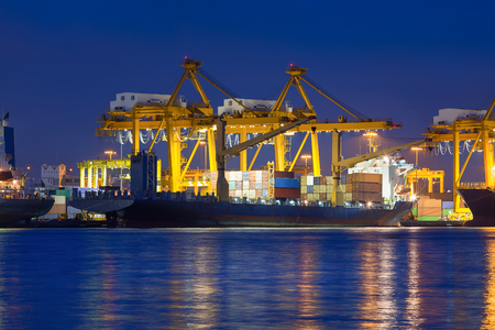Cargo ship and crane at port reflect on river, twilight time. photo