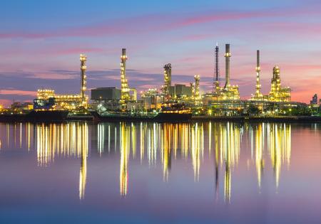 Erdölraffinerie reflektiert auf dem Fluss in der Dämmerung.