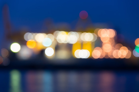 Bokeh of cargo ship and crane at port reflect on river, twilight time. photo