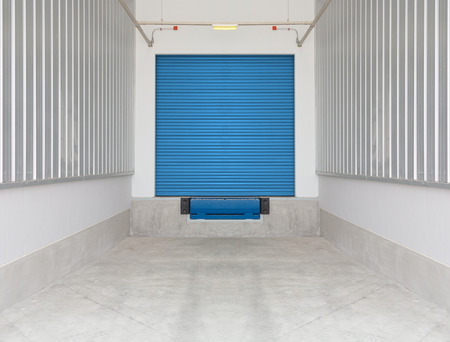 Dock leveler and shutter door outside factory, blue color. photo