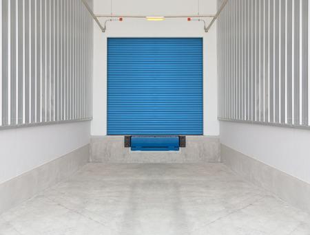 leveler: Dock leveler and shutter door outside factory, blue color. Stock Photo