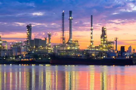 destilacion: Refinería de petróleo refleja en el río en el crepúsculo.