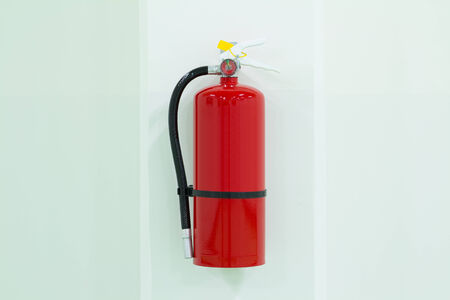 fire extinguisher: Fire extinguisher on white wall.