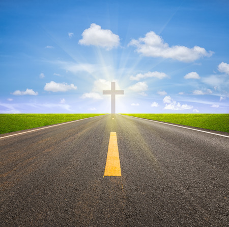 Asphalt road and crucifix with blue sky background. photo
