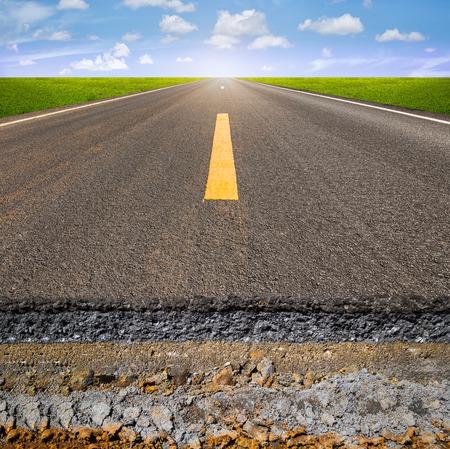 Sezione di strada asfaltata con sfondo blu del cielo.