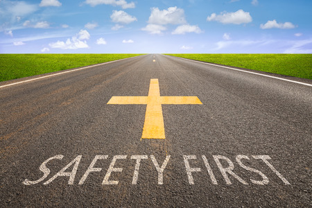 safety: Perspective of asphalt road with safety first text. Stock Photo