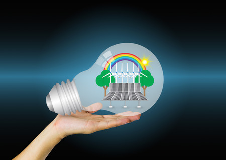 solarcell: Bulb and alternative energy in hand with blue background.