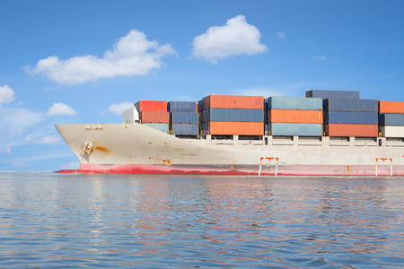 seafaring: Cargo ship and cargo container in sea with clear sky background.