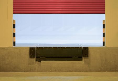 checkerplate: Ramp or dock leveler and shutter door outside factory.