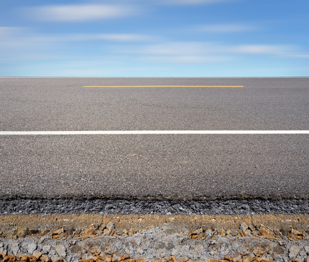 pavement: Cross section of asphalt road with blue sky background. Stock Photo