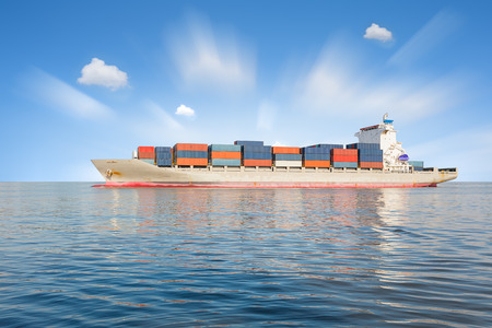 freighter: Cargo ship and cargo container in sea with clear sky background.