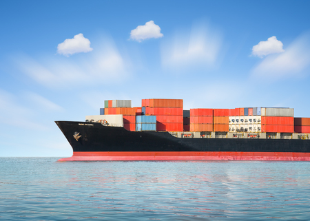 freighter: Cargo ship and cargo container in sea with sky background.