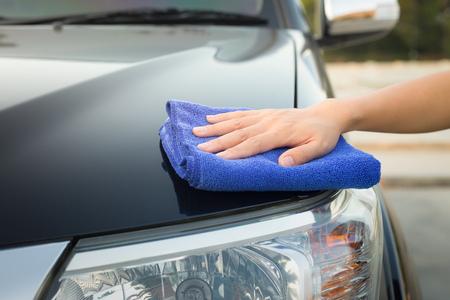 少女の手が車の表面を拭きます。