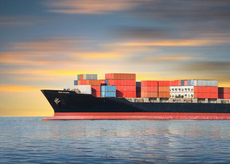 Vrachtschip en lading containers in zee met lucht achtergrond.
