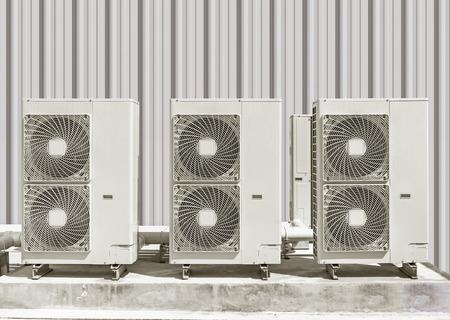 사이딩 벽 배경 콘크리트 받침대에 공기 압축기.