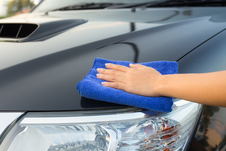 clean car: Girls hand wiping on surface of car. Stock Photo