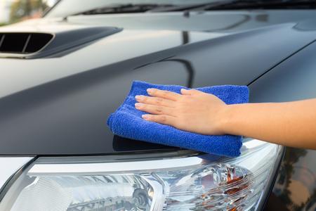 laves: La mano de limpieza de la muchacha en la superficie del coche.