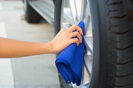 women's hand: Womens hand wiping on alloy Wheels.