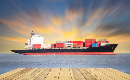 sea side: Cargo ship and cargo container in sea with sky background.