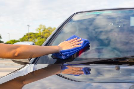 女性の手が車の上を拭きます。