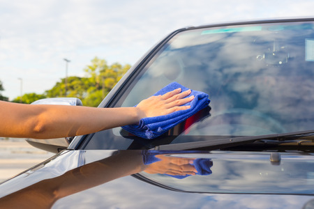 car glass: Womens hand wiping on car.