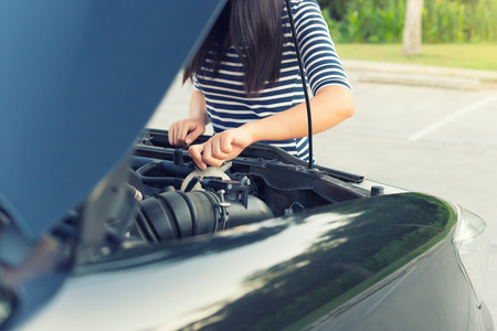 Women checking coolant level of car.