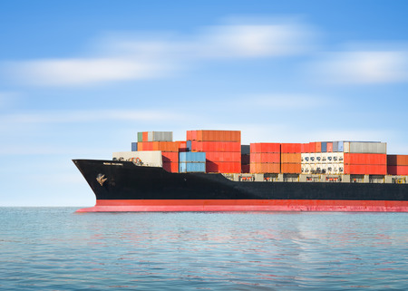 sea freight: Cargo ship and cargo container in sea with sky background.